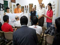 """Participants presented Father Mintoff, founder of Peace Laboratory, with a banner that states: """"We Can Save the World, We Can Change the Situation."""""""
