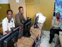 Migrants hang out in the Internet café at the Marsa Open Center